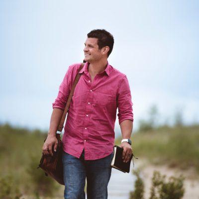 A man wearing a pink shirt walking holding a bible