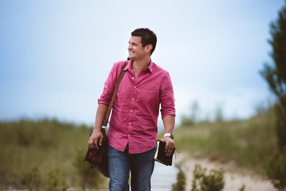 A man wearing a pink shirt walking holding a bible