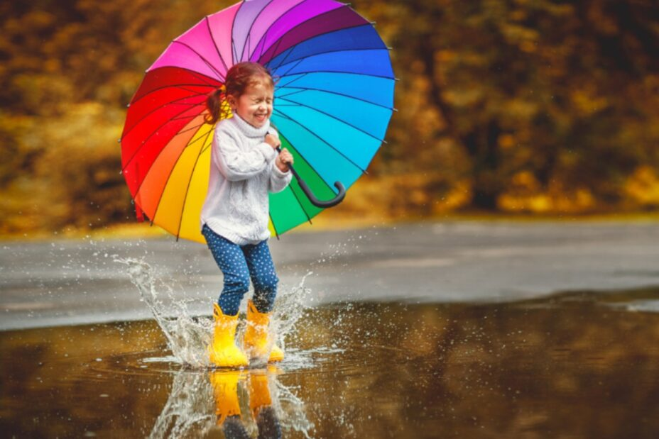 A young girl with a colourful umbrella jumping in puddles