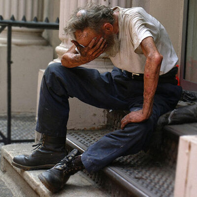 A homeless man with his head in his hands