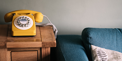 Yellow telephone on side table beside sofa