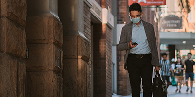 Man wearing face mask walking down the street and checking his phone