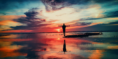Man standing on rocks with arms outstretched looking at sunrise