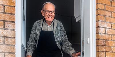Elderly man opening door