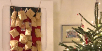 Advent calendar hanging with a Christmas tree next to it