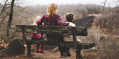 Woman and two children sitting on a bench