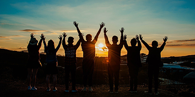Row of young people with arms in the air in front of a sunset