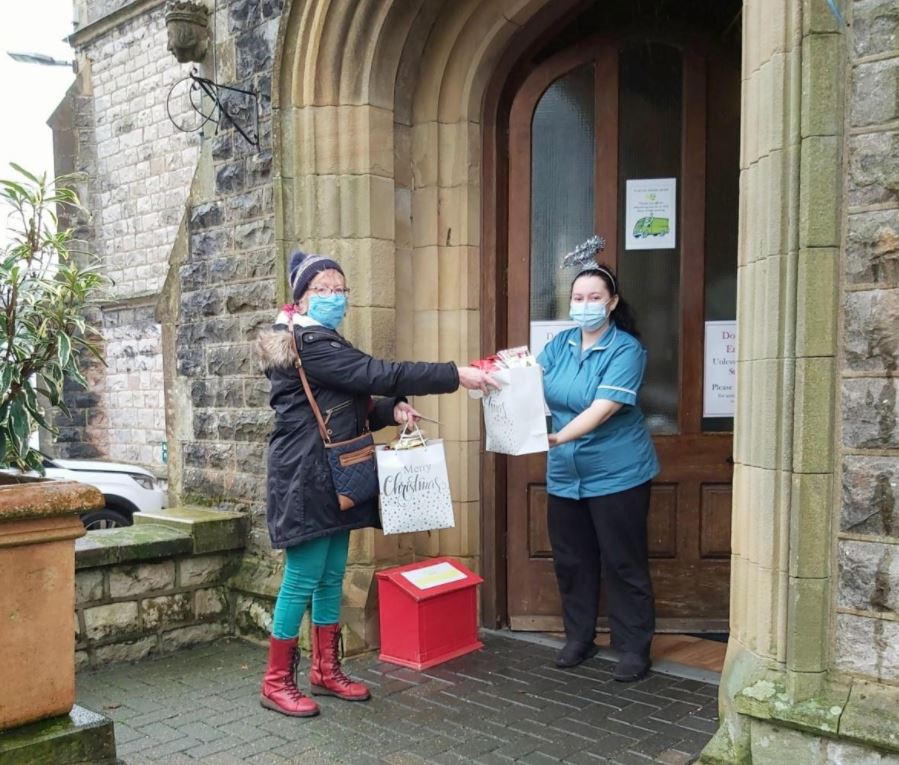 Anna Chaplain hands over a gift bag of knitted crosses to a member of staff outside a care home.
