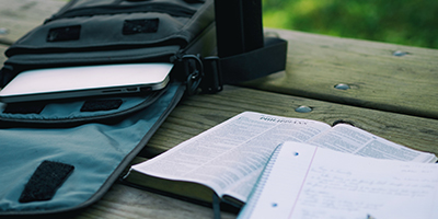 Open Bible with laptop bag and notebook on an outdoor table