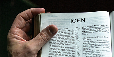 Hand holding open a Bible at the gospel of John