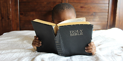 Boy reading Bible while lying on bed