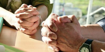 Man's and woman's hands in prayer