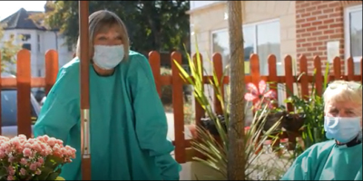 Debbie Thrower visiting a care home in a face mask and gown