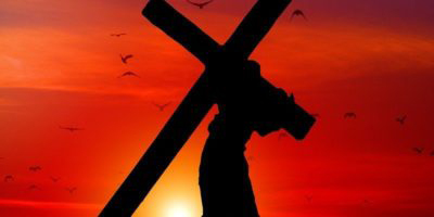 Man going up a hill carrying a cross, silhouetted against a sunset
