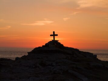 Cross on a mountaintop with a sunset in the background