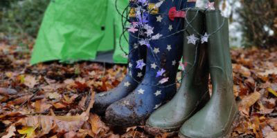 Wellington boots next to a tent in woodland