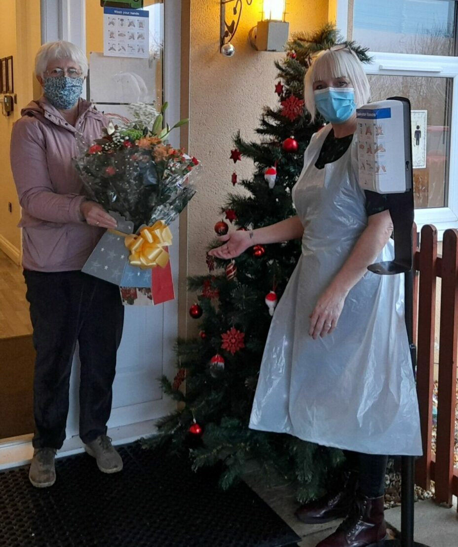 Anna Chaplain presents flowers to a care home worker
