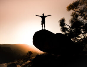 A person standing on top of a mountain with their arms out