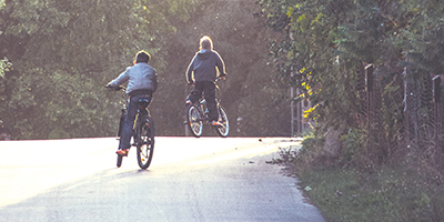 Two boys riding bicycles on a road